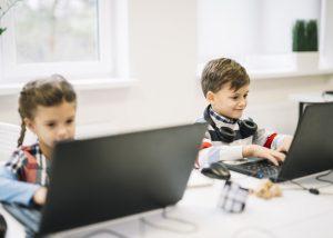 glimlachend-portret-van-een-jongen-die-laptop-zitting-met-een-meisje-in-het-klaslokaal-met-behulp-van_23-2148039908