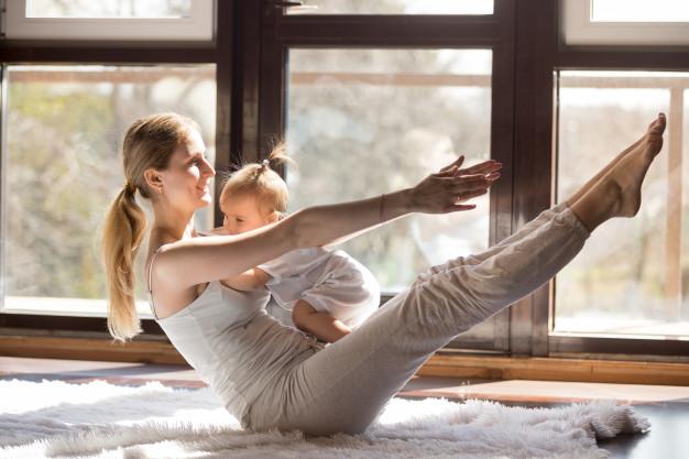 de-jonge-yogiamoeder-in-boot-stelt-met-haar-weinig-dochter_1163-4436